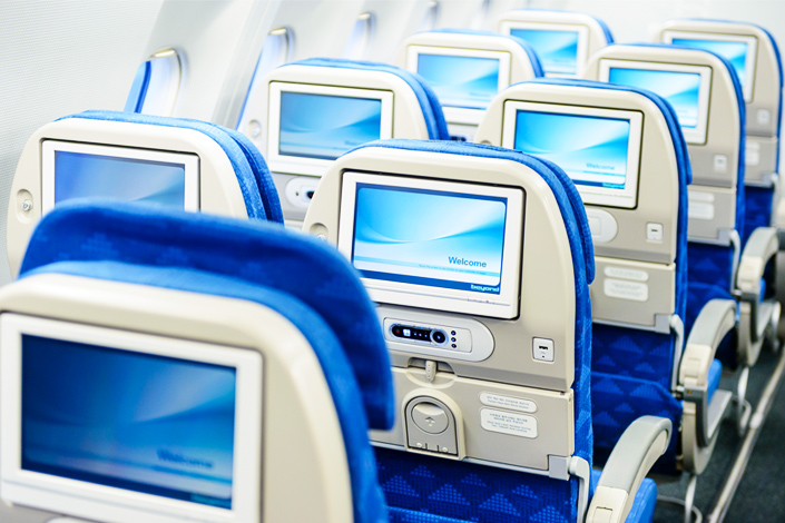 Rows of empty passenger seats with screens on board an aircraft