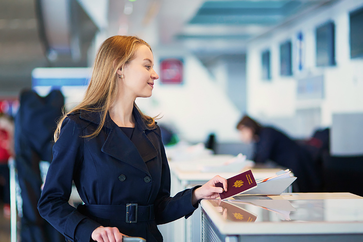 A young woman with a passport in her hand checking in for her flight at an airport check-in desk