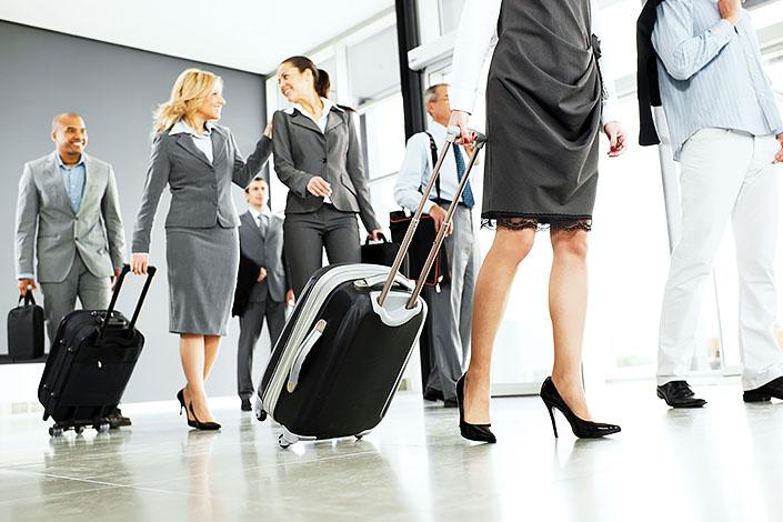 Группа женщин и мужчин в деловых костюмах проходит через зал аэропорта