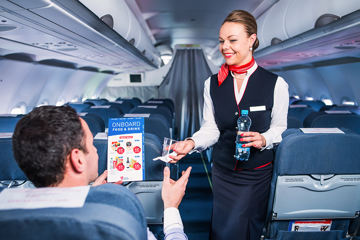 A passenger about to sit down in their pre-ordered preferred seat aboard a Czech Airlines aircraft while being offered refreshments by a flight attendant