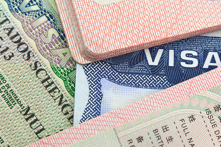 A close-up view of travel documents and passports with visas
