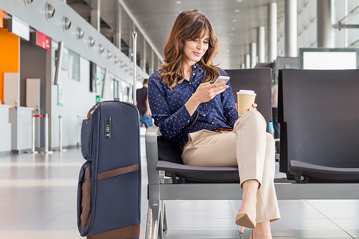 A young woman using her mobile phone while sitting beside her baggage in an airport hall waiting for boarding