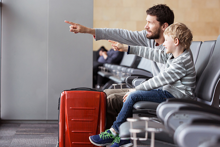A father and his son sitting in an airport hall beside their baggage, watching aircraft and waiting for boarding