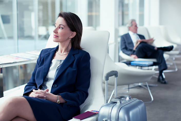 A young woman sitting beside her baggage in an airport lounge waiting for boarding