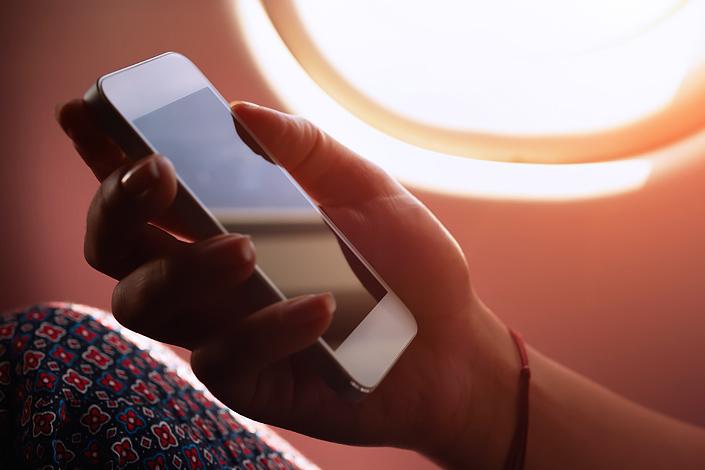 """Una mujer sentada en la cabina de un avión con un teléfono móvil en la mano con el modo """"Avión / Vuelo seguro"""" activado"""
