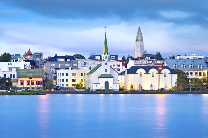 Reykjavik - una vista de una iglesia tradicional de madera en la orilla de una bahía, con la iglesia Hallgrimskirkja al fondo